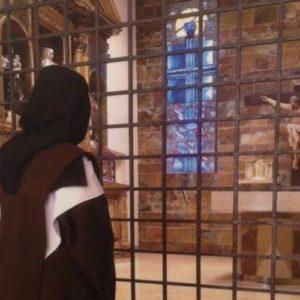 Una de las hermanas, mirando a Cristo a través de la reja.